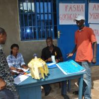 Un des deux points de collecte des contributions sur l'avenue Kitenge. Le vice-président de la Mutanga Iwacu Club, Eddy Frank Nceke (tricot noir), reçoit un à un les Bakunzi ba Mutanga ©Iwacu