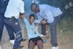 Ce jeune ne peut plus pas se lever, blessé aux jambes : un officier de la police et un passant l'aident à se relever ©O.N/Iwacu