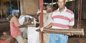 Ephraïm Ndayishima devant un concasseur. A sa gauche, des sacs contenant des briquettes à vendre ©Iwacu