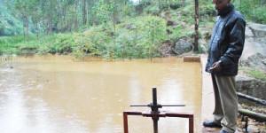 Léonidas Ndikuryayo, membre de l'association pour le développement du centre de Rutabo, nous fait découvrir le lac de retenue de la micro-centrale hydroélectrique ©Iwacu