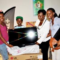 Jeanne Nduwimana recevant un téléviseur écran-plat en compagnie de ses enfants