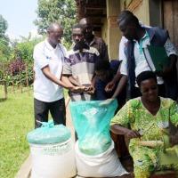 Du haricot conservé dans un « sac pic ». Une femme fait tourner une égreneuse manuelle de maïs  fournie par IFDC ©Iwacu