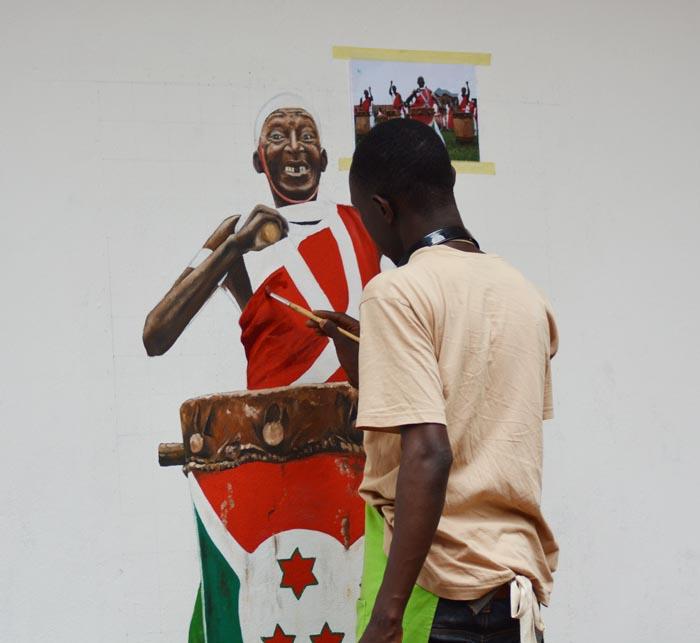 """Sur un mur du Centre Culturel ,  Clovis Ngoy, un jeune artiste  peint  Antime, le gardien de la mémoire des tambours de Gishora. """"J'ai voulu rendre hommage au vieux Mutimbo de son vivant » explique Antoine Kaburahe ©Iwacu"""