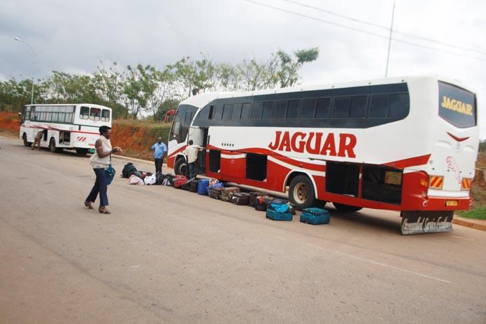 Pour question de contrôles, les chauffeurs  ouvrent les soutes des bus avant de passer le poste frontalier  de Gasenyi ©Iwacu