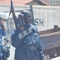 Alors que les autres policiers n'ont que des matraques, celui-ci a trois chargeurs sur son fusil ©Iwacu
