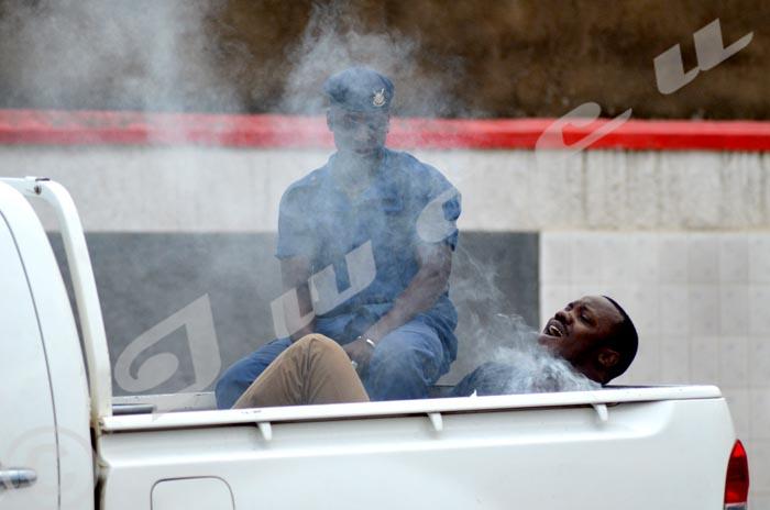 Un policier se surprend à jouer avec une grenade lacrymogène entre les jambes d'un manifestant arrêté