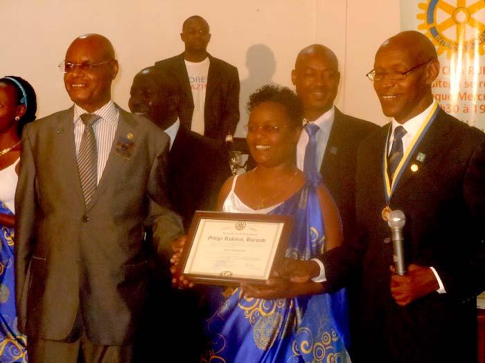 La présidente recevant la charte devant les invités et les nouveaux rotariens ©Iwacu