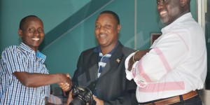 Mardi, le président du CNC remet un appareil photo et un badge au journaliste d'Iwacu Onesphore Nibigira (à gauche). Ce matériel avait été injustement confisqué par un policier de la garde présidentielle, il y plus d'un mois. Antoine Kaburahe, directeur des publications d'Iwacu (à droite) remercie M.Giramahoro qui a réglé la question en moins de 48heures ©F.N/Iwacu