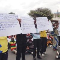les mainfestants exhibant des affiches devant l'Ambassade de Belgique