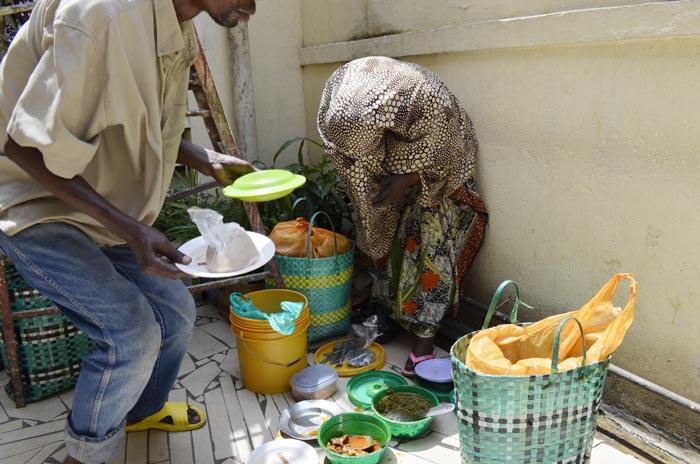 Une marchande ambulante de nourriture cuite en train de servir ses clients.