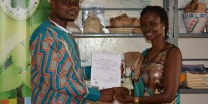Le président du RJAP remettant le certificat à Ginette Karirekinyana