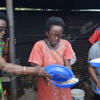 Christine Ntahe (au milieu) entrain de servir à manger
