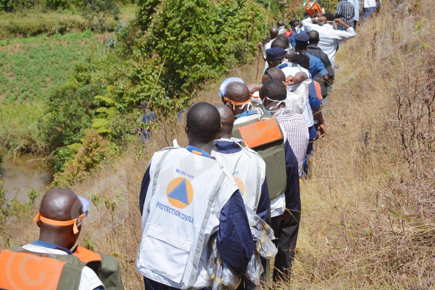 En fil indienne, journalistes, agents de la protection civile et du CNIDH escaladent les collines pour aller repêcher les deux corps