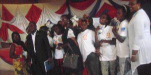 Les jeunes filles serviettes hygiéniques à la main posent avec le gouverneur de Rumonge, la représentante de l'Ambassade des USA  et la coordinatrice de Sacode