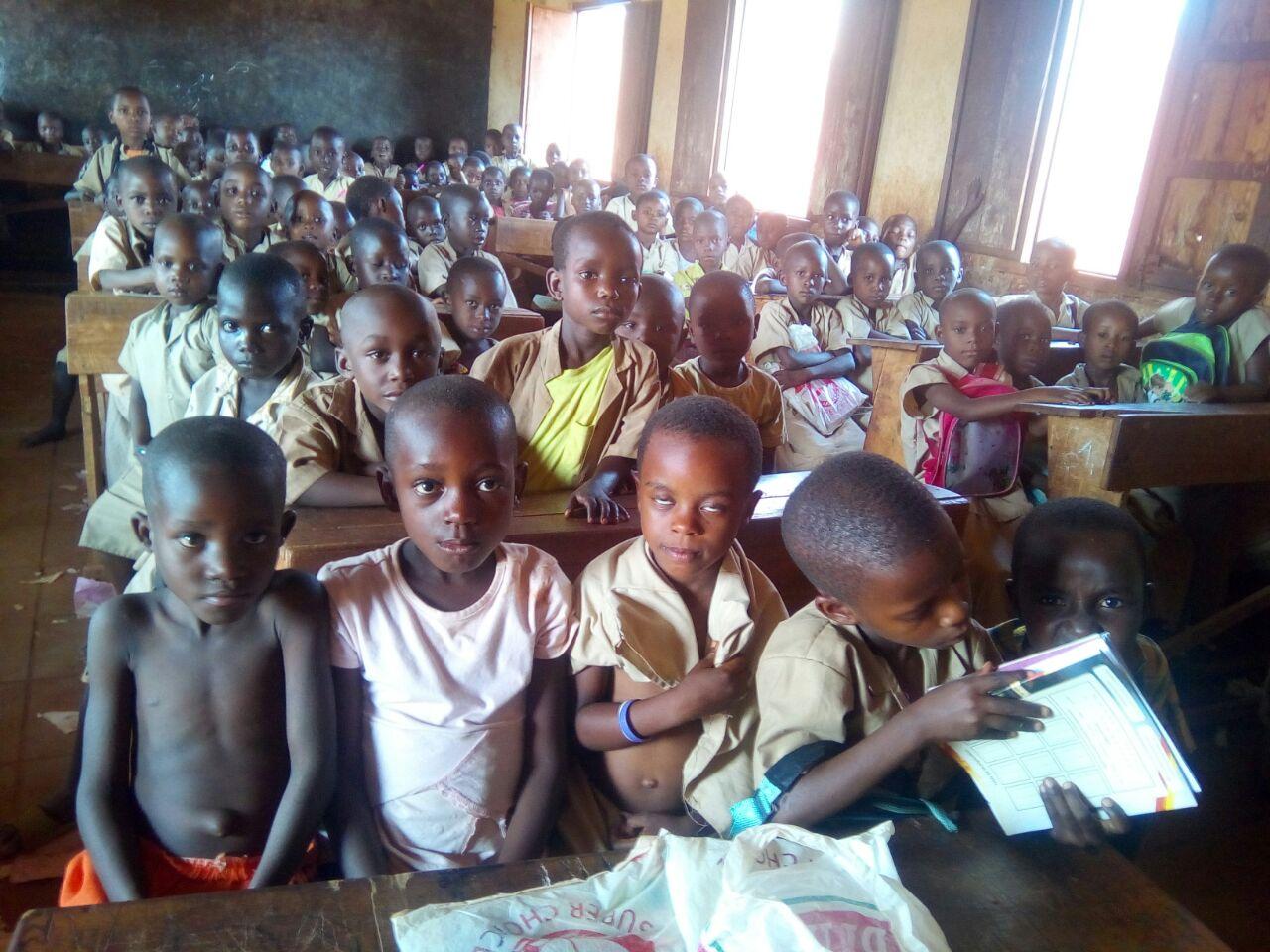 Cinq écoliers de la première année partagent le banc pupitre