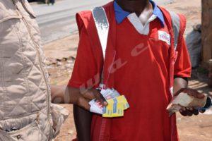 Un vendeur de crédits de recharge téléphonique en train de chercher un billet de 100Fbu en bon état.