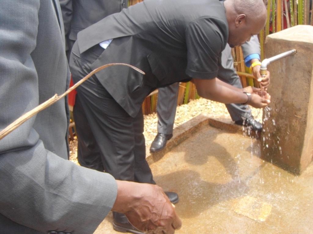 Un représentant de la Croix Rouge Burundi en train de boire l'eau captée de la colline Nyabigina