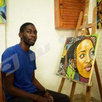 Christian Bujiriri donnant des détails sur un tableau  qui sera exposé