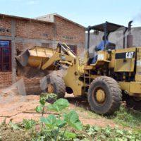Un bulldozer passant à la destruction de la maison d'Emmanuel Bizimana