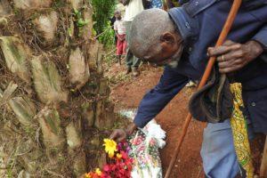 Cérémonies de dépôt de gerbes de fleurs sous un palmier, la fosse commune se trouve juste à côté