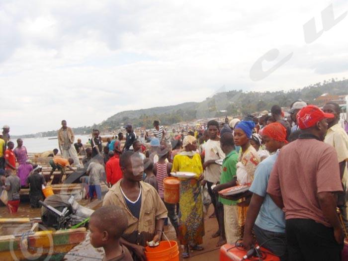 Commerçants et consommateurs se bousculent vers les pirogues pour acheter le peu de poissons pêchés.
