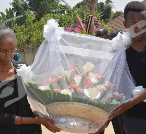 Arnaud Igor Giriteka (à droite) et Anaïs Hashazinka, deux plus jeunes journalistes d'Iwacu déposent une gerbe de fleurs. Photo prise dans les enceintes d'Iwacu le 22 juillet 2018 ©Onesphore Nibigira/Iwacu