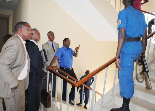 Deux policiers barrent le chemin à Me Isidore Rufyikiri et ses avocats dans les escaliers des bureaus du parquet général près la cours anti-corruption  ©Iwacu