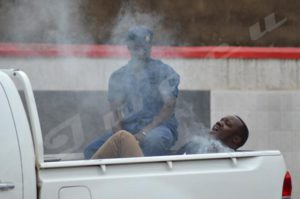 An arrested young man suffering ill-treatment in the police vehicle