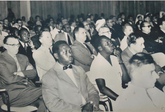 Le Prince Louis Rwagasore en pleine réunion du Conseil général du Ruanda-Urundi tenue au Palais des arts en juin 1959. A l'extrême gauche son pire ennemi Albert Maus(en lunettes, les bras croisés), président de l'Association des Colons du Ruanda-Urundi. Un défroqué qui hérita une grande fortune de son père. Il finançait au Rwanda le PARMEHUTU de Grégoire Kayibanda et l'APROSOMA de Joseph Gitera