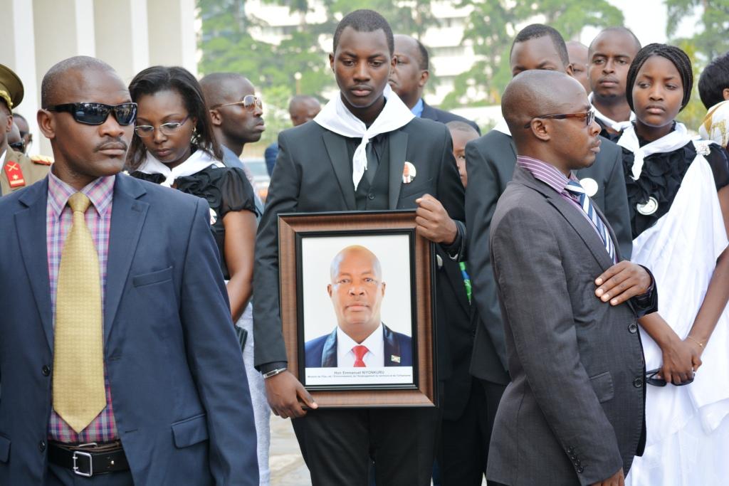 Un des fils d'Emmanuel Niyonkuru tient une photo de son père devant la Cathédrale Régina Mundi.