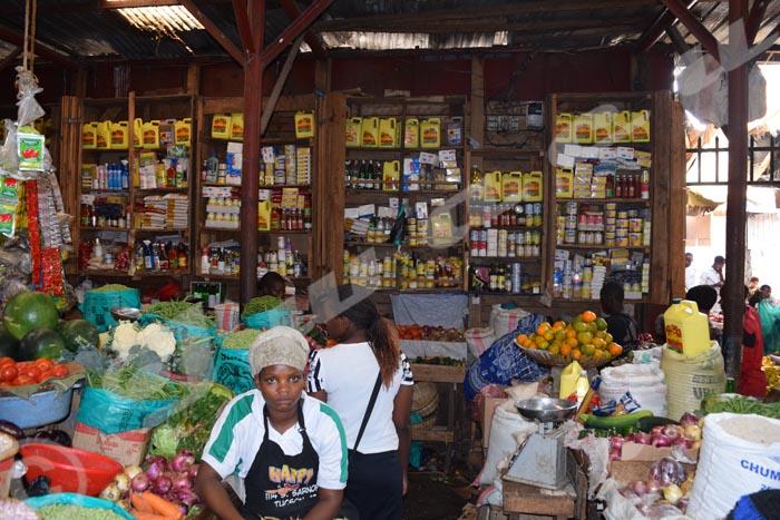Une vendeuse d'un commerce achalandé, en attente de clients.